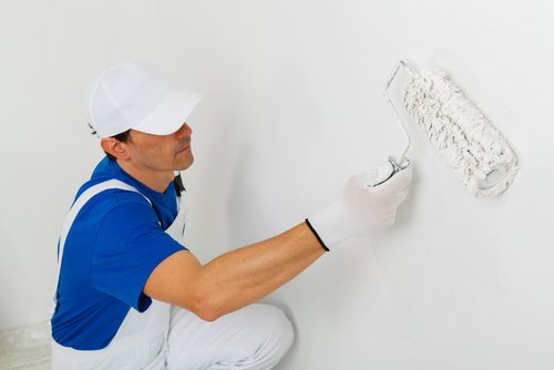 Man painting wall white