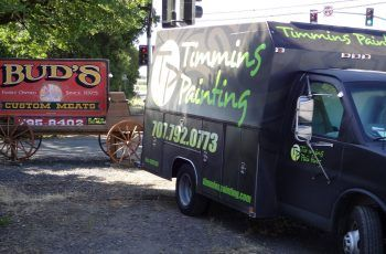 Timmins Painting truck infront of Bud's Custom Meats sign