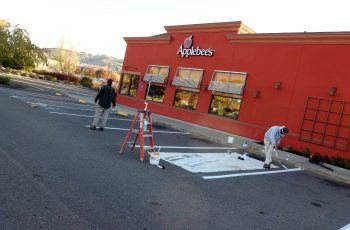 Timmins painting employees painting Applebee's parking spots