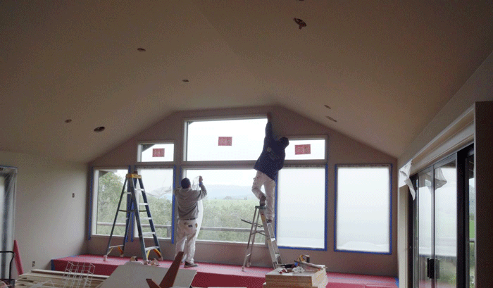Two painters painting the interior of a home