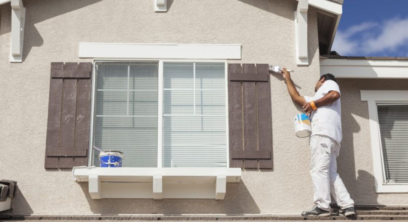 Busy House Painter Painting the Trim And Shutters of A Home.