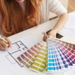 Closeup of woman with red hair and white blouse working on choosing color paint for her house.