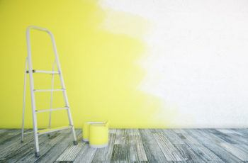 Step ladder and paint cans in front of partially painted interior wall.