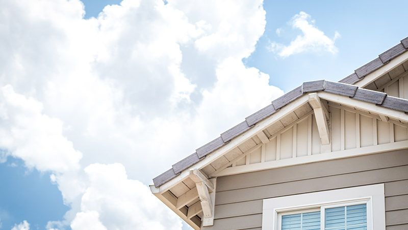 looking up at the second story of a house with blue sky and clouds behind it