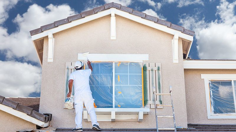 professional painter on roof of home painting the trim with white paint