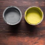 Cans with paint of ultimate gray and illuminating color on brown wooden background. Colors of 2021 year.