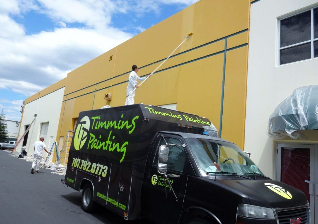 Timmins Painting Truck with Employees painting commercial building